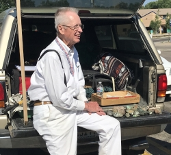 Colorado Mineral Society (CMS) member and field trip leader Don Bray sits on the tailgate of his pickup next to a box of mineral specimens he has collected during 30 years of visits to the Sedalia Mine.